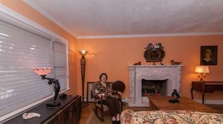 Marion Tucker sits in the living room of