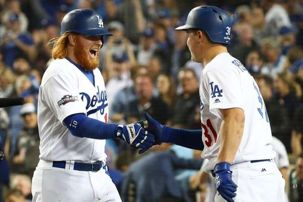 Former Met Justin Turner, left, is greeted by