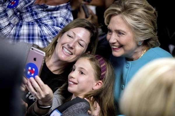 Democratic presidential candidate Hillary Clinton takes a photograph