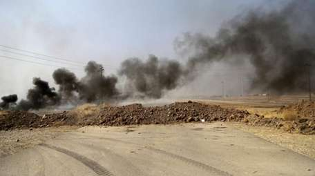 Smoke rises from Islamic State positions after an