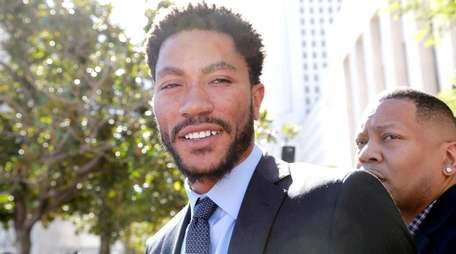 NBA star Derrick Rose smiles as he leaves