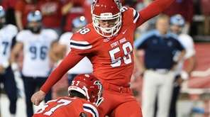Stony Brook kicker Przemyslaw Popek kicks for an