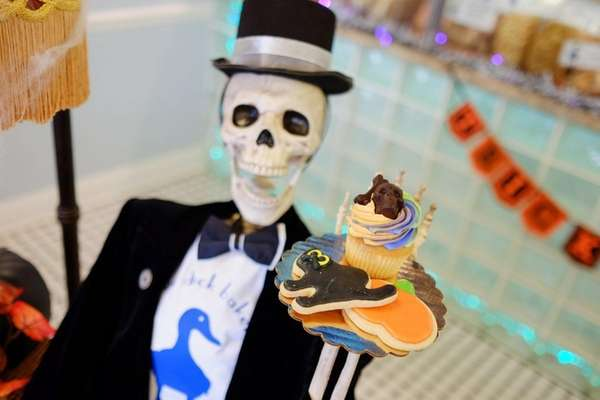 A skeleton holds holiday-themed cookies and cupcakes at