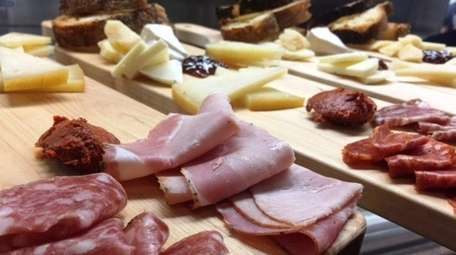 Boards of assorted meats and cheeses are on