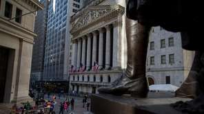 Pedestrians walk past the New York Stock Exchange