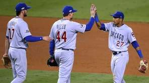 Chicago Cubs' players Addison Russell, right, Anthony Rizzo,