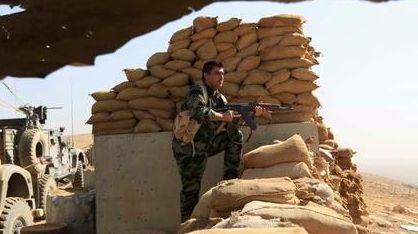 An Iraqi Kurdish Peshmerga fighter stands guard outside