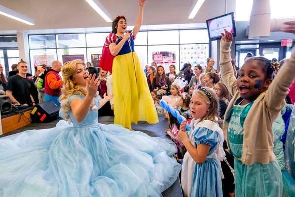 Children watch a collection of Disney princesses perform