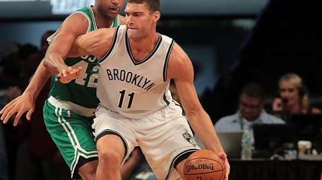 Nets center Brook Lopez (11) works against