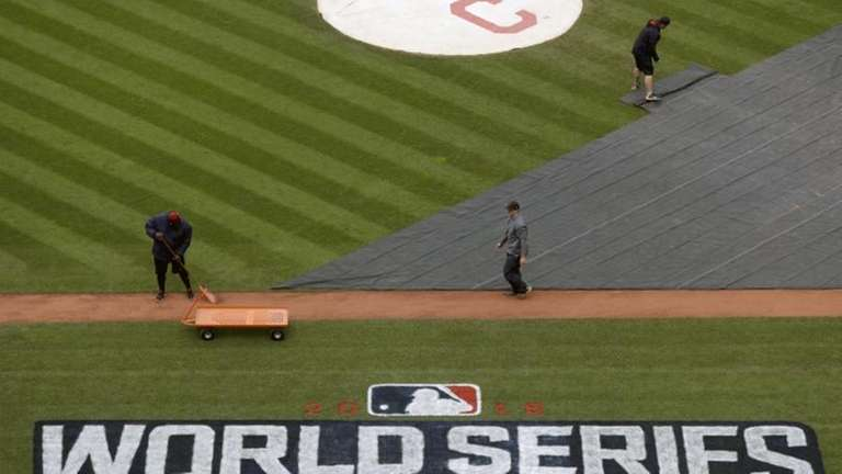 Members of the grounds crew prepare the field