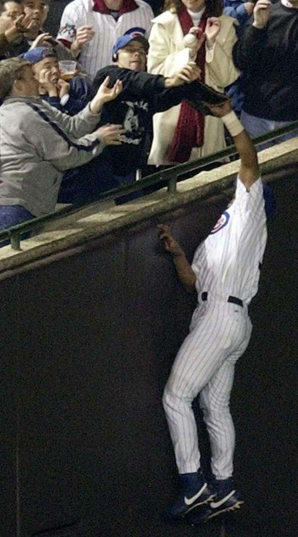 Chicago Cubs leftfielder Moises Alou reaches into the