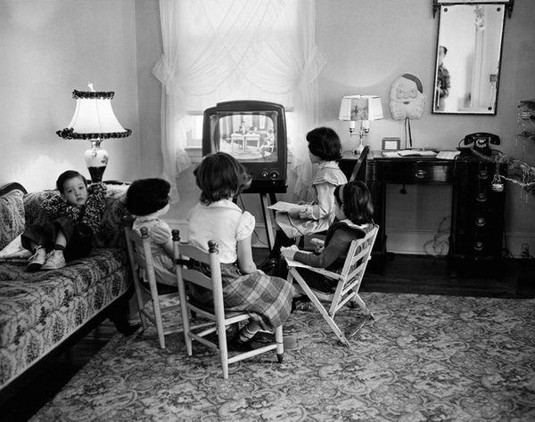 Children gather around a television set in 1953,