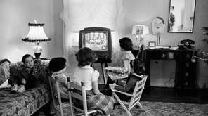 Children gather around a television set in 1953,