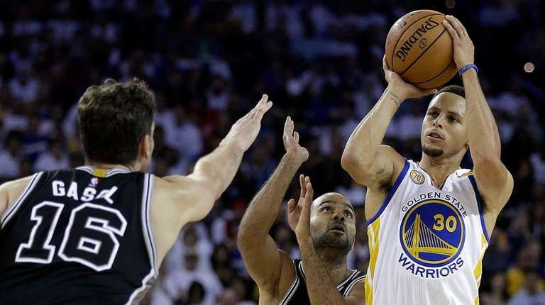 Golden State Warriors' Stephen Curry, right, shoots against