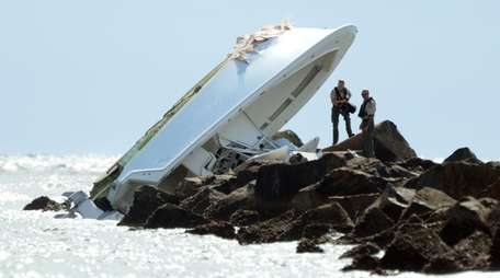 Law enforcement officials inspect a boat overturned on