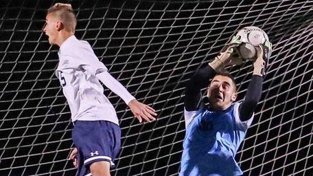 Syosset goalie Matthew Sobel gets the save between