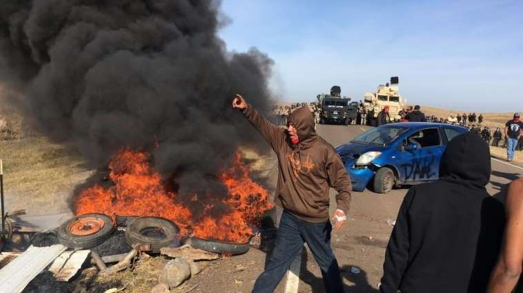 Demonstrators stand next to burning tires as armed