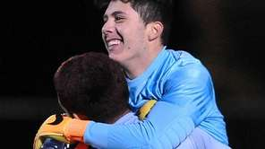 Glen Cove goalie Cris Henriquez, right, gets congratulated