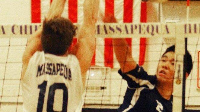 Massapequa's Alec Helford blocks a spike by Plainview