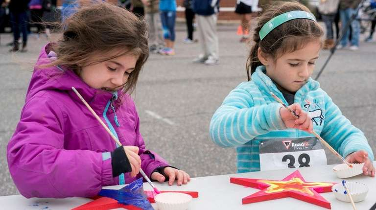 From left, Calie Spitz, 5, paints with Sydney