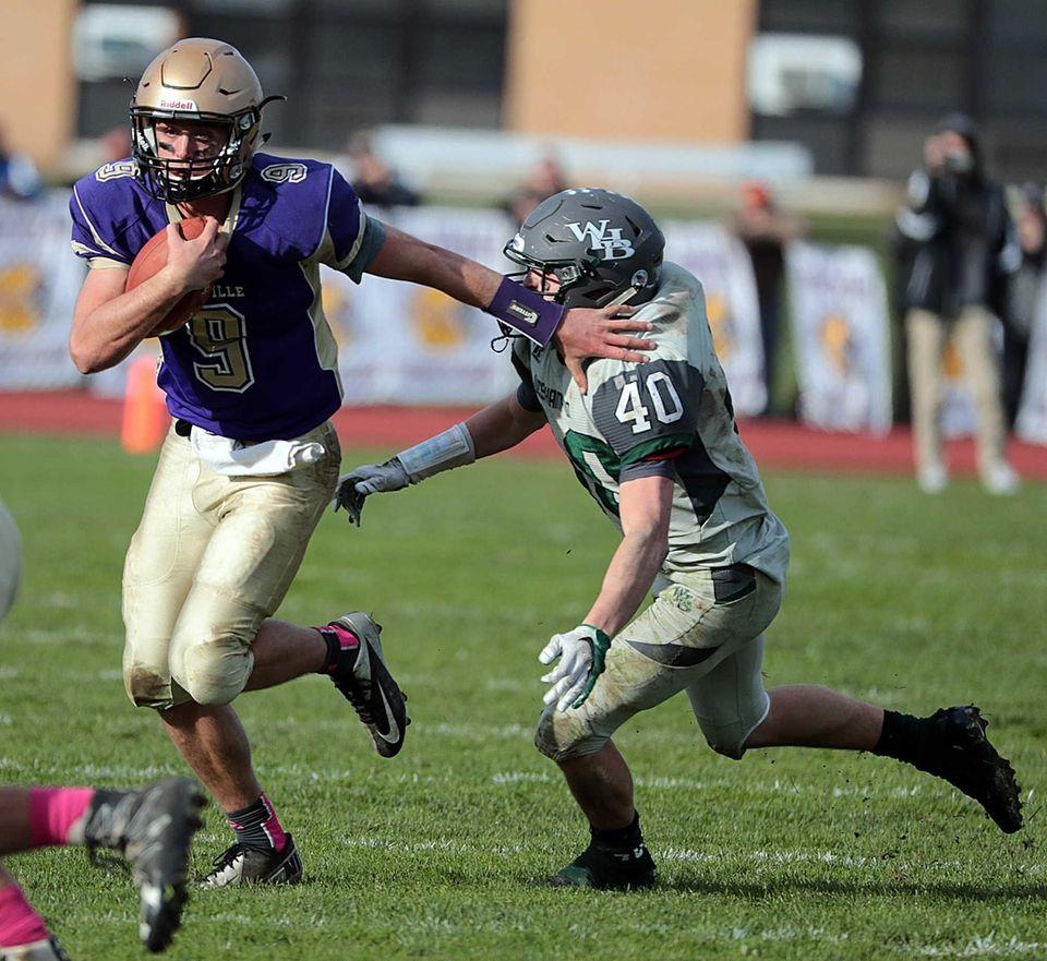 Sayville quarterback Jack Coan (9) stiff arms Westhampton