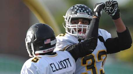 Frankie Stola #33 of Northport, right, gets congratulated