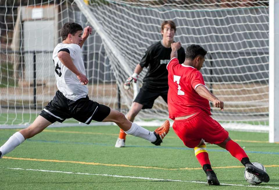 Center Moriches' Eric Amaya (right), takes a shot