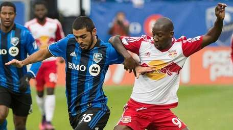 Montreal Impact's Victor Cabrera, left, challenges New York