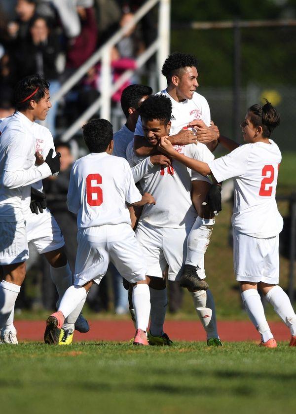 Amityville's team celebrates Marlon Martinez's first of two