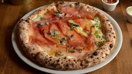 This white pizza sports mozzarella, speck, fontina and