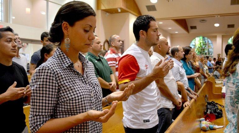 Parishioners raise their hands in prayer during a