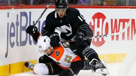 Shane Prince finishes a check against Flyers' Shayne