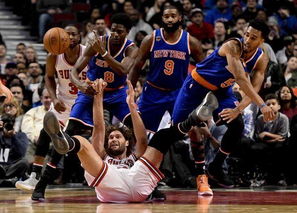 Chicago Bulls center Robin Lopez, bottom, passes the
