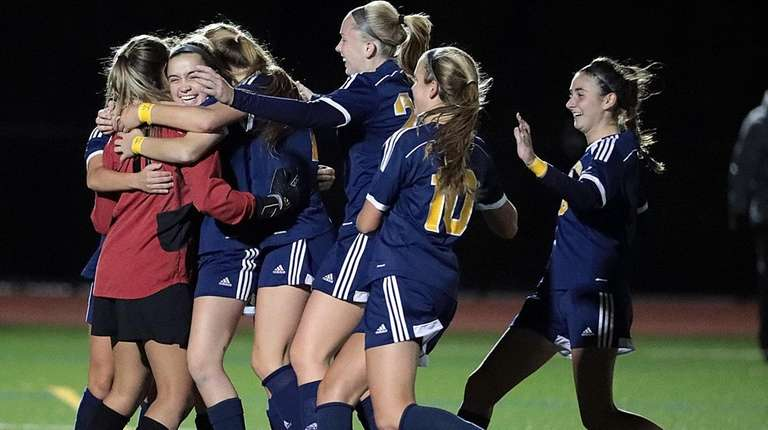 Massapequa players mob goalkeeper Haylee Poltorak after the