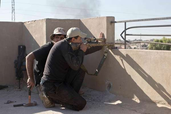 An Iraqi special forces sniper searches for a