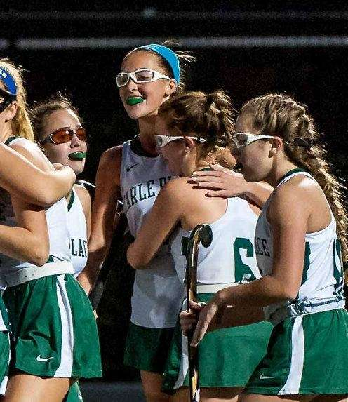 Carle Place's Gianna McKeough (4) hugs her teammates