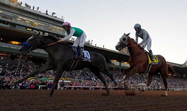 Arrogate with jockey Mike Smith, left, wins the