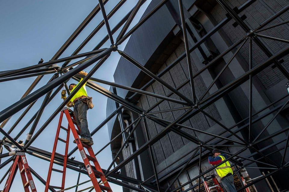 Construction workers at Nassau Coliseum assemble the structures