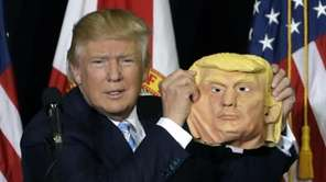 Republican presidential candidate Donald Trump holds up a
