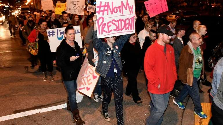Protesters holds up signs in opposition of Donald