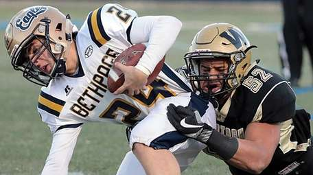 Bethpage halfback Chris Greco (24) is stopped for