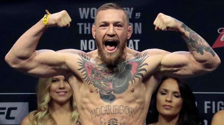 Conor McGregor stands on a scale during the