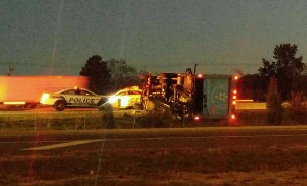 A tractor trailer lies on its side along