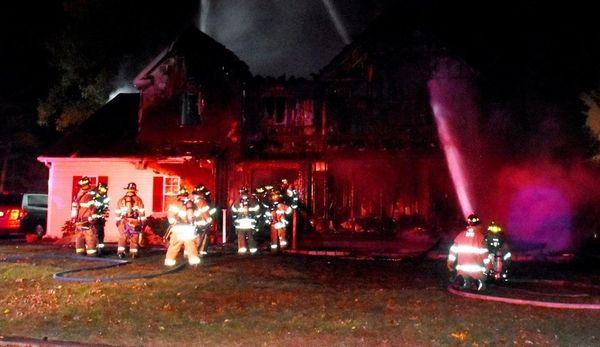 Firefighters battle a blaze that gutted a house
