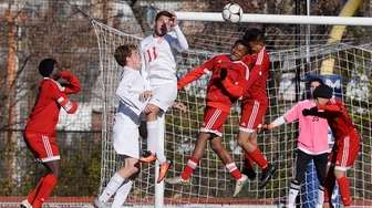Amityville players clear a corner kick during a