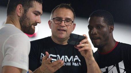 Trainer Mark Henry, center, shows former UFC middleweight