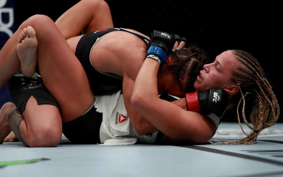 Liz Carmouche of the United States, top, fights