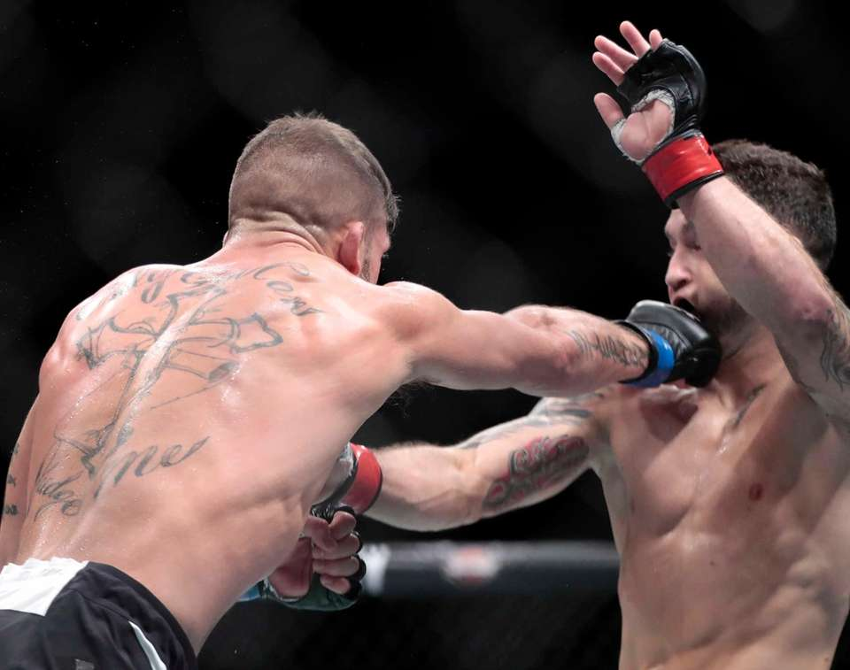 Jeremy Stephens, left, connects with a punch to