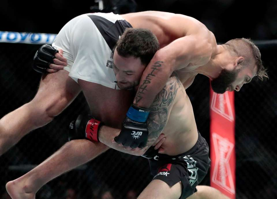 Frankie Edgar, bottom, lifts Jeremy Stephens during a