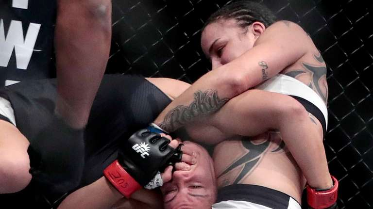 Raquel Pennington, right, grabs at Miesha Tate during